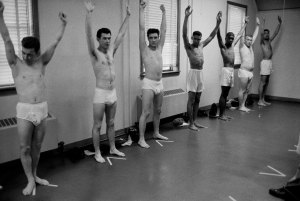 ALASKA, UNITED STATES - MARCH 1958:  Wearing only underwear, singing star turned US Army Pvt. Elvis Presley (3L) raises his arms along with several other inductees during an inspection at Ft. Chaffee.  (Photo by Don Cravens/The LIFE Images Collection/Getty Images)