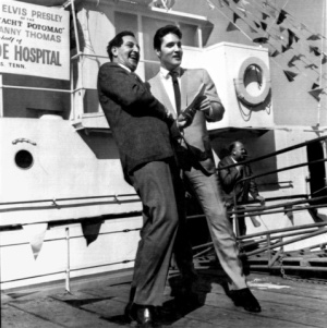 Elvis Presley turns over the papers for the S.S. Potomac, former presidential yacht of the late President Franklin D. Roosevelt to Danny Thomas, founder of St. Jude Hospital February 14, 1964 in Long Beach, CA. Presley purchased the yacht to keep it from being scrapped. Thomas accepted the boat for St. Jude, a non-sectarian project dedicated to finding cures for catastrophic diseases of children. It is hoped that the boat will be sold as soon as possible and the money used in research for children's diseases. Presley's manager, Col. Tom Parker, is in the background. ( UPI )