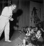 15 Nov 1956, Las Vegas, Nevada, USA --- Original caption: Las Vegas, Nevada: Liberace Serenades Elvis. In his first appearance since his European tour, Liberace and his troupe favors special ringside guest Elvis Presley with a number at the Riviera early today. after the show, Elvis joined Liberace backstage for an impromptu jam session in which Elvis played the piano and Liberace the guitar. --- Image by © Bettmann/CORBIS