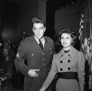 Rook 'n' roll singer Elvis Presley, his army stint nearly at an end, is greeted at Ft. Dix. New Jersey on March 3, 1960, by the 19-year-old daughter of Frank Sinatra. Nancy Sinatra was on hand to greet Presley who flew in from Germany for discharge. Presley's first TV appearance will be on the Frank Sinatra show. (AP Photo)