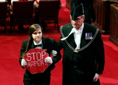 Senate page Brigette DePape is led from the room by Sergeant-at-Arms Kevin Vickers as Canada's Governor General David Johnston delivers the Speech from the Throne on Parliament Hill in Ottawa